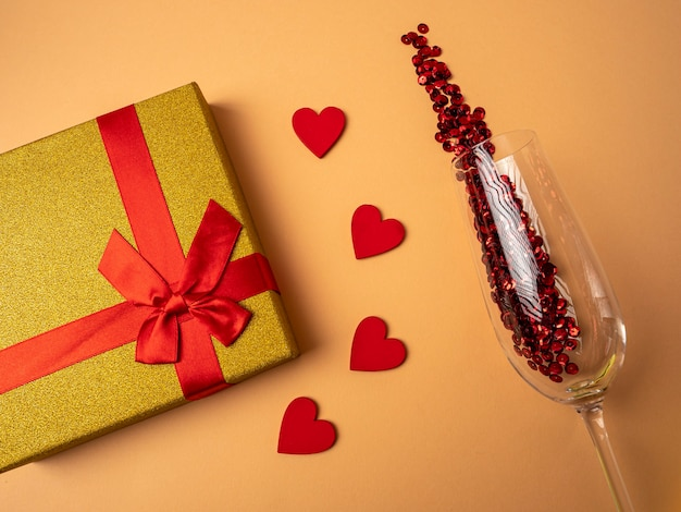 A yellow gift with a ribbon in the form of a butterfly knot lies next to four red hearts and a glass with red sparkles on an orange background