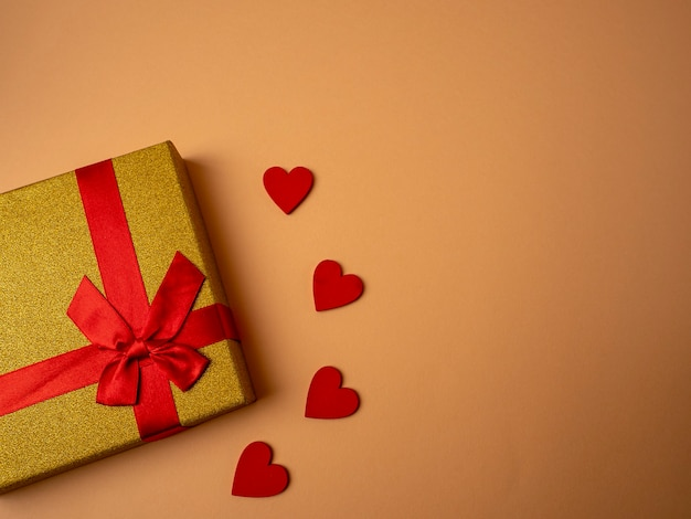 A yellow gift with a ribbon in the form of a butterfly knot lies next to four red hearts on a nice orange background