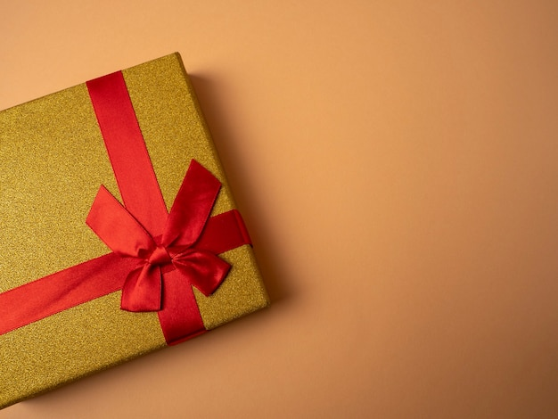 Yellow gift with a ribbon in the form of a butterfly knot lies on a nice orange background