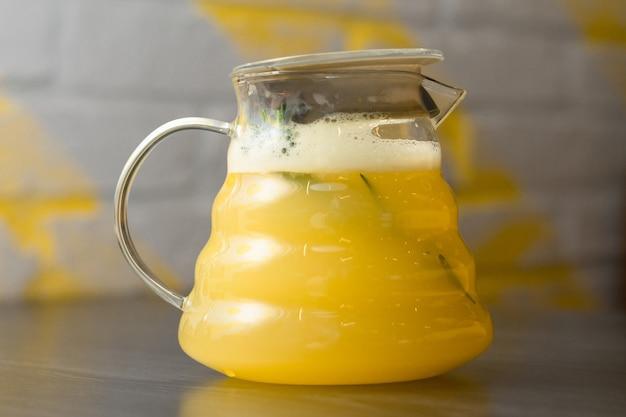 Желтый имбирный чай с лимоном и веткой розмарина в прозрачном чайнике на деревянном столе