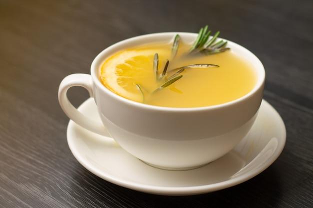 Желтый имбирный чай с лимоном и веткой розмарина в белой чашке на деревянном столе