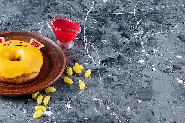 Ciambella smaltata gialla con caramelle di fagioli posta su un tavolo di marmo.