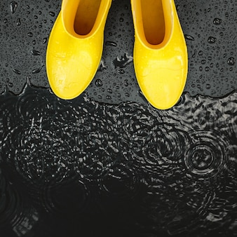 Yellow glossy gumboots stand in the rain on black