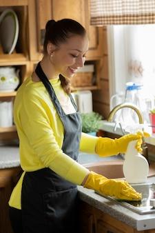 Желтая перчатка девушка с распылителем вытирает поверхность плиты с тканью. уборка дома