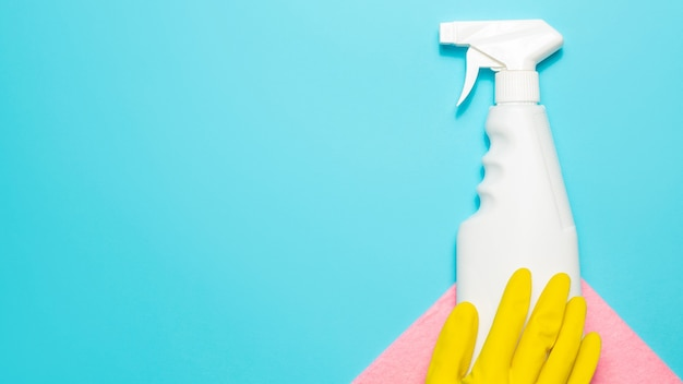 Yellow gloves, microfiber cloth and spray cleaner on a blue background, top view, copy space. cleaning supplies.