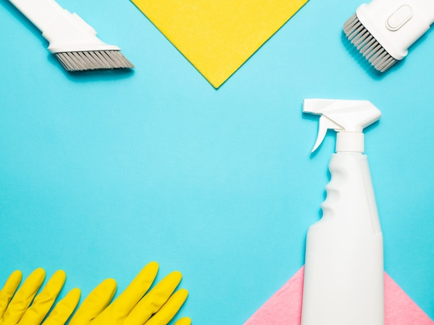 Yellow gloves, microfiber cloth, vacuum cleaner attachments and spray cleaner on a blue background, top view, copy space. cleaning supplies.