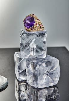 Yellow gold ring with amethyst on ice cubes on a gray background with reflection. jewelry art and product sales