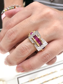 エレガントな長い指で若い女性の手に白いダイヤモンドとイエローゴールドのルビーリングがクローズアップ