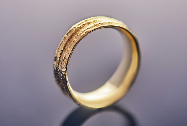 Yellow gold wedding ring with an unusual texture standing on gray