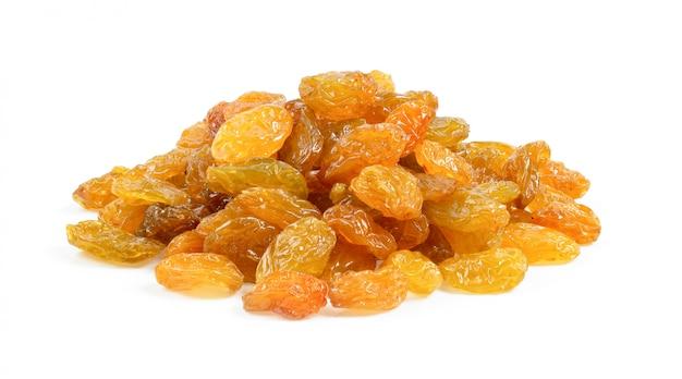 Yellow golden raisins on white wall