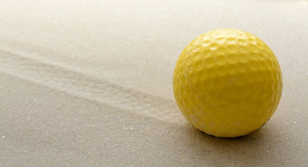Yellow golf ball on the sand background