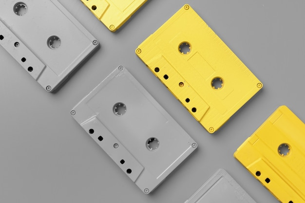 Yellow and gray audio cassettes on gray top view copy space
