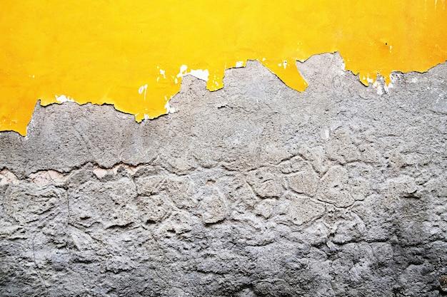 벽돌 벽에 노란색, 회색 파괴 석고. 초라한 페인트 배경으로 그런 지 시멘트입니다.