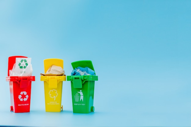Желтые, зеленые и красные корзины с символом корзины на синем фоне. держите город в порядке, оставляет символ утилизации. концепция охраны природы.
