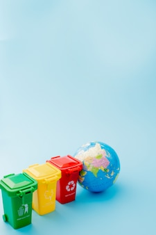 파란색 배경에 재활용 기호로 노란색, 녹색 및 빨강 휴지통. 도시를 깔끔하게 유지하고 재활용 기호를 남겨 둡니다. 자연 보호 개념
