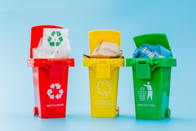 파란색 배경에 재활용 기호로 노란색, 녹색 및 빨간색 휴지통. 도시를 깔끔하게 유지하고 재활용 기호를 남깁니다. 자연 보호 개념.