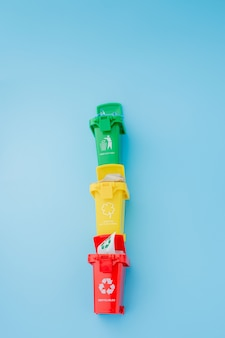파란색 배경에 재활용 기호가 있는 노란색, 녹색 및 빨간색 휴지통. 도시를 깔끔하게 유지하고 재활용 기호를 남깁니다. 자연 보호 개념입니다.