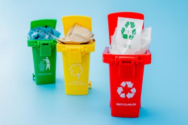 Желтые, зеленые и красные корзины с символом переработки на синем