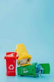 Желтые, зеленые и красные корзины с символами утилизации