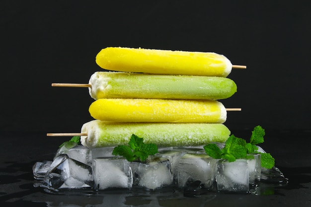 Yellow and green fruit ice cream on a stick with mint on ice on a black table.