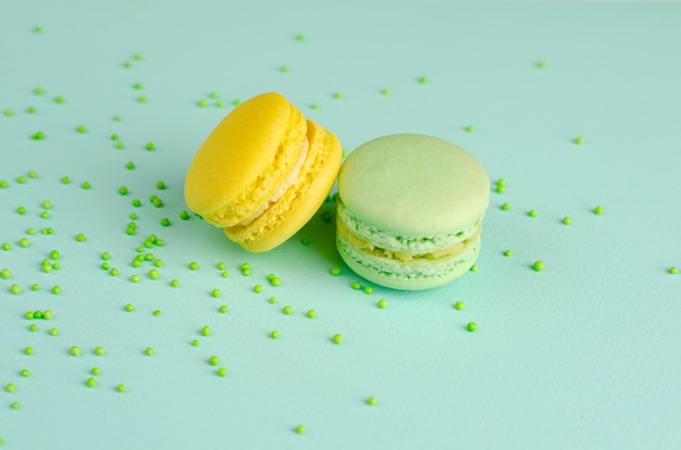 Yellow and green macaroons or macarons on pastel mintwith sprinkles