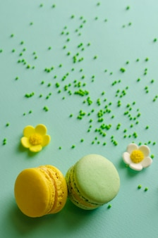 Yellow and green macaroons on pastel mint decorated with sprinkles