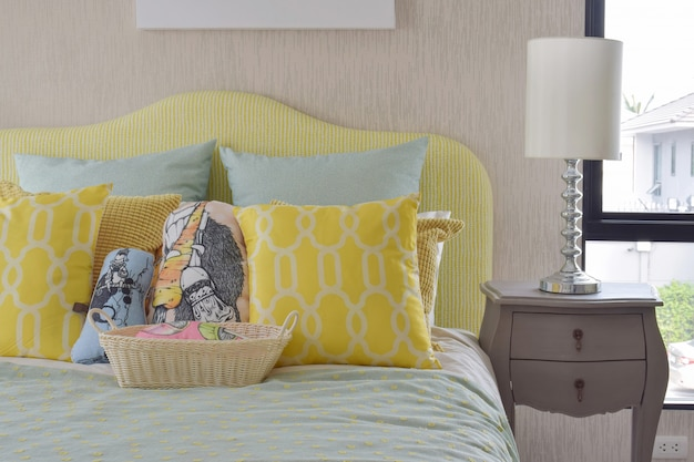 Yellow and green and pattern pillows on classic style bed