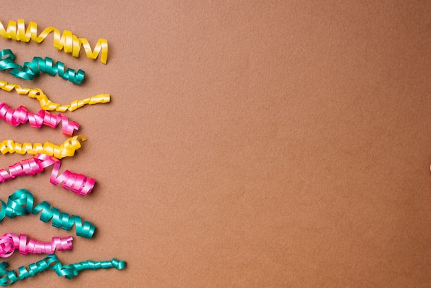 Yellow; green and pink streamers on brown background