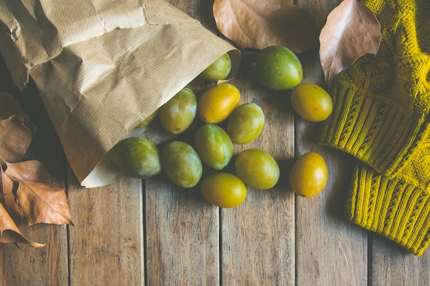 Yellow green plums in brown kraft paper bag scattered
