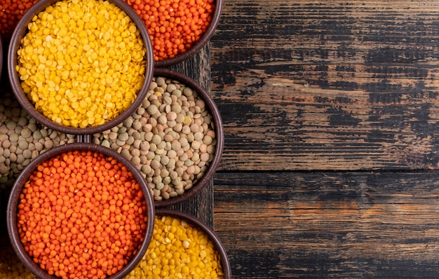 Yellow, green and red lentils in a brown bowls close-up on a dark wooden table