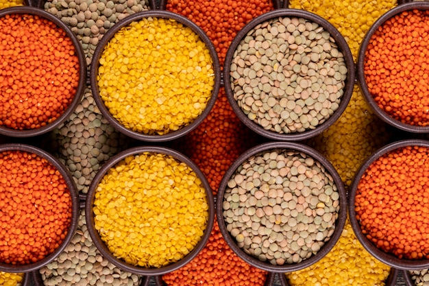 Yellow, green and red lentils in a brown bowls close-up