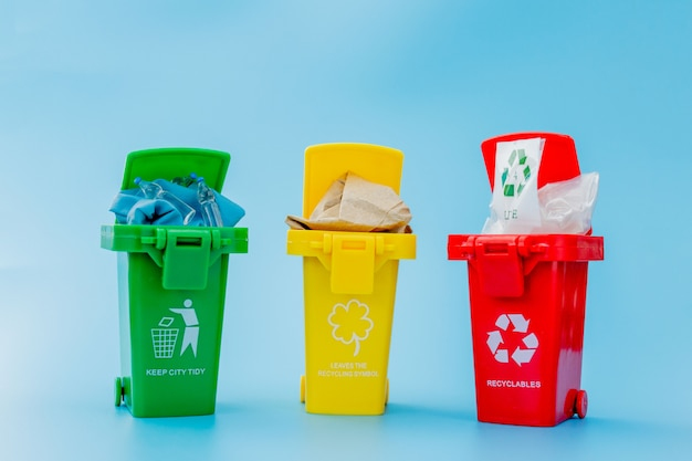 Yellow, green and red recycle bins with recycle symbol on blue background.