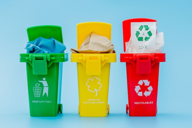 Yellow, green and red recycle bins with recycle symbol on blue.