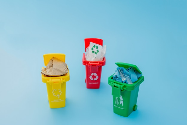 Yellow, green and red recycle bins with recycle symbol on blue
