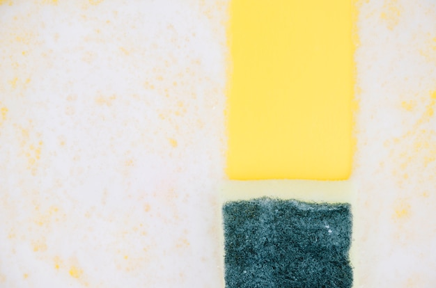 Yellow and green sponges on white soap sud