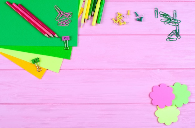 Yellow and green stationery and felt on pink wooden background.