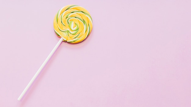 Yellow and green striped lollipop against pink background