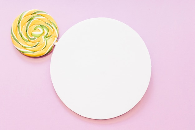 Yellow and green striped lollipop over the white circular frame against pink background