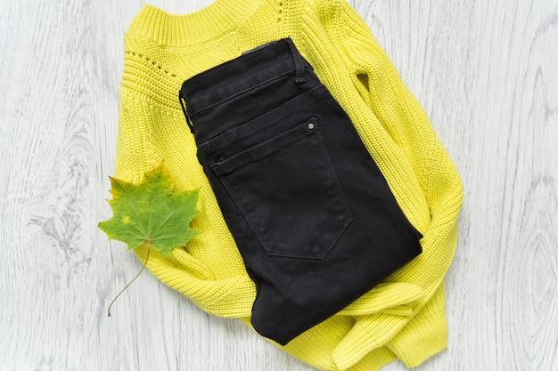 黄緑色のセーターと黒のジーンズ。ファッショナブルなコンセプト