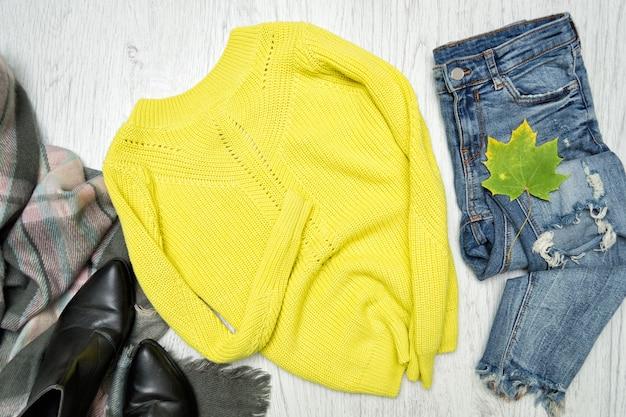 黄緑色のセーター、スカーフ、ジーンズ。ファッショナブルなコンセプト