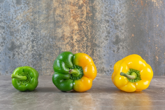 Yellow and green sweet bell peppers on marble background.