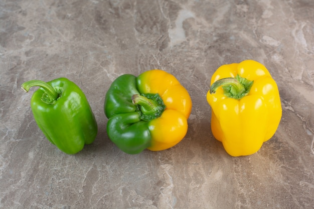 Yellow and green sweet bell peppers on marble surface