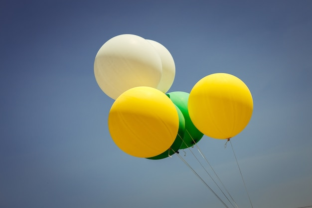 Yellow, green and white balloons fly in the sky