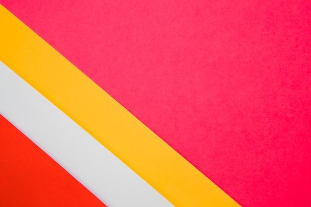 Giallo; carte di cartone colorato grigio e rosso su sfondo rosa