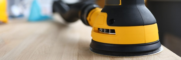 Yellow grinding machine polishes wood close up and make smooth