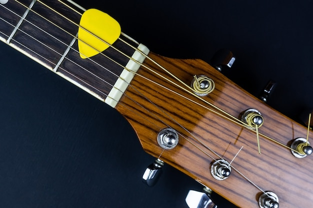 Yellow guitar pick tucked into gold acoustic guitar strings on a dark wood fret board.