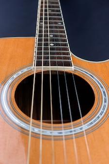 Желтый медиатор заправлен в золотые струны акустической гитары