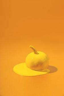 Желтая тыква на хэллоуин с жидкой краской течет минимальный праздничный сезон оранжевый концептуальный фон