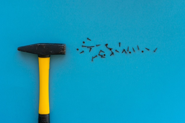 Yellow hammer and nails are scattered on the blue surface, workspace, construction layout