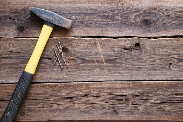 Yellow hammer on a natural wooden background